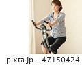 フィットネスバイクで体を鍛える女性 47150424