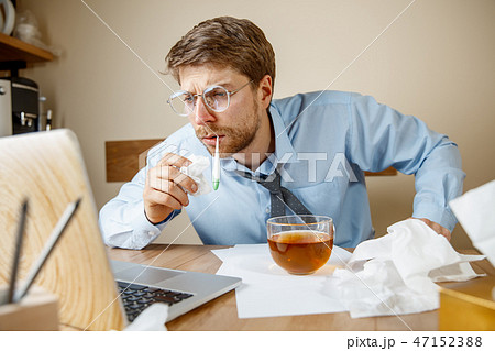 Sick man while working in office, businessman caught cold, seasonal flu. 47152388