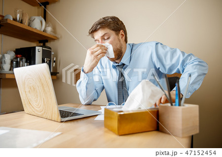 Sick man while working in office, businessman caught cold, seasonal flu. 47152454