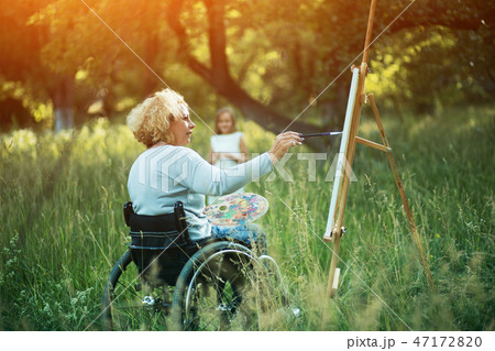 Woman in wheelchair drawing on easel outside 47172820