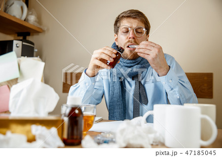 Sick man while working in office, businessman caught cold, seasonal flu. 47185045