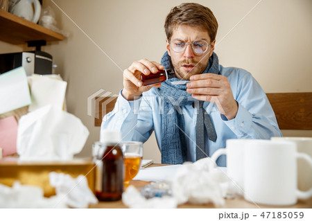 Sick man while working in office, businessman caught cold, seasonal flu. 47185059