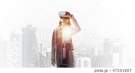 Woman in mask against sunrise above city trying virtual reality 47201607