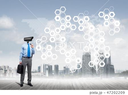 Camera headed man standing on wooden floor against modern cityscape 47202209
