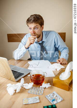 Sick man while working in office, businessman caught cold, seasonal flu. 47210359