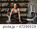 Young happy fitness woman doing leg stretching exercise 47290529