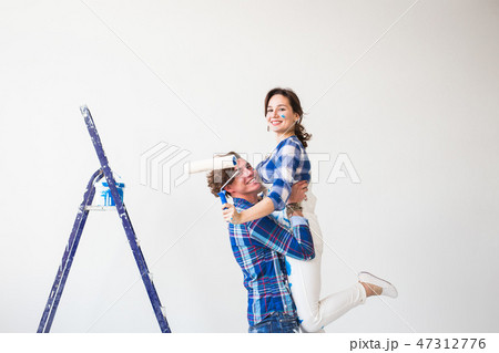 Renovation, redecoration and family concept - Young man holds young woman in his arms during 47312776
