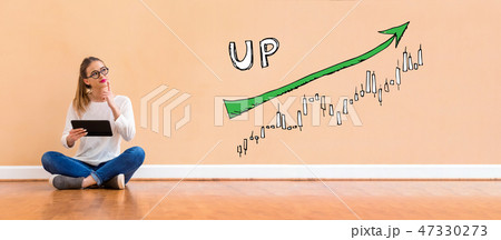 Market up trend chart with woman using a tablet 47330273