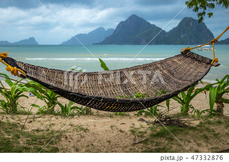 Traditional braided hammock in the shade with tropical island in the background 47332876