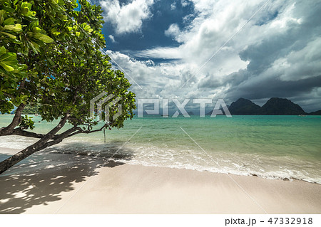 Tropical beach with trees, clouds sky, turquoise water and white sand in El Nido, Philippines 47332918