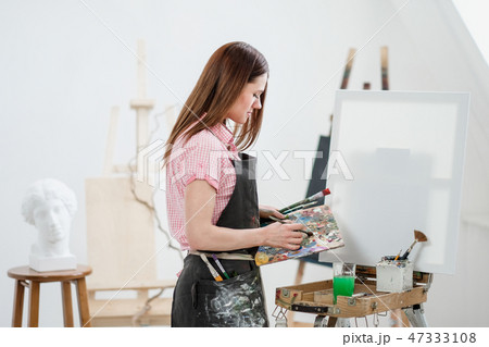 A young woman painter in a bright white studio draws a picture on canvas on an easel. 47333108