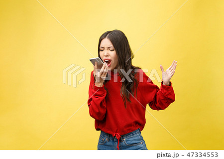 Portrait angry young asian woman disappoint at mobile phone while standing over yellow background 47334553