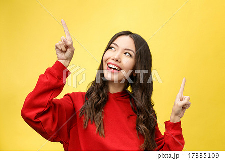 Young beautiful asian woman pointing to copyspace, isolated on yellow background 47335109