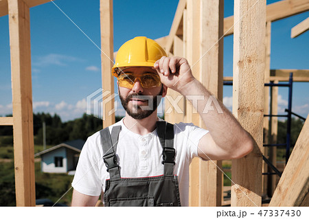 The man is a builder on the roof of a wooden frame house. 47337430