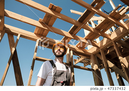 The man is a builder on the roof of a wooden frame house. 47337432