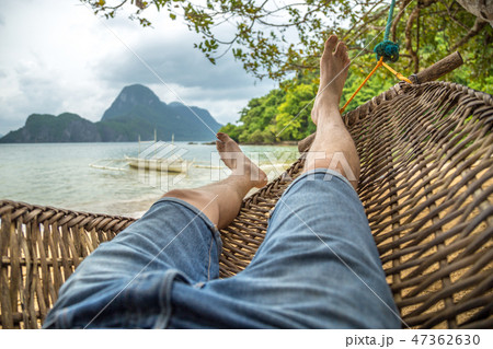 Relaxing in the hammock, nude feet close up, cloudy summer day at mountain and sea background 47362630