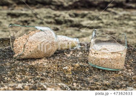 Broken bottle of beer on the sand beach 47362633