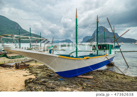 Old fishing boat is being repaired on the shore in rainy weather in El Nido, Palawan, Philippines 47362638