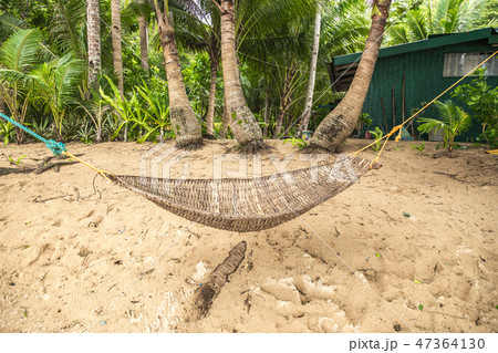Traditional braided hammock in the shade with tropical island in the background 47364130