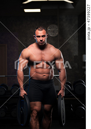 Male bodybuilder with naked torso posing in gymの写真素材