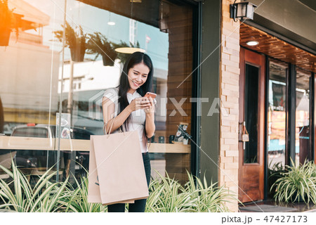 young woman texting while enjoying a day shopping 47427173