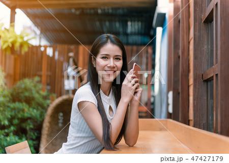 Asian woman hands holding coffee mug 47427179