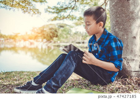 Young boy reading a book while sitting in the park 47427185