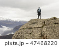 Alone hiker with backpack standing on rocks  47468220