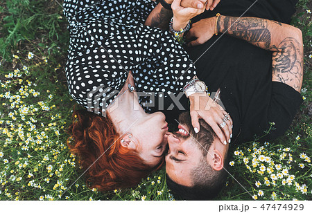 Young couple lies on the field with daisies. 47474929