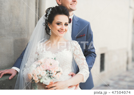 Lovely happy wedding couple, bride with long white dress posing in beautiful city 47504074