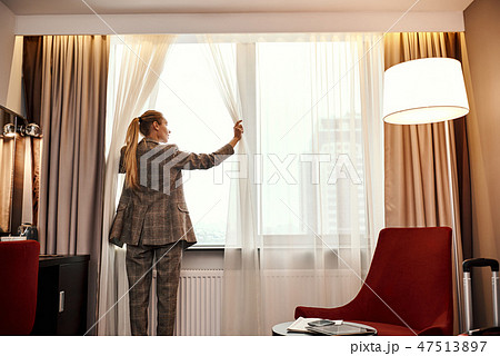 Businesswoman in dark hotel room opens curtains on window to the morning light 47513897