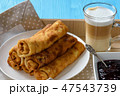 Sweet cheese stuffed pancakes and  cup of coffee. 47543739