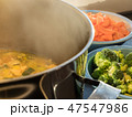 Steaming soup pot with broccoli and carrots 47547986