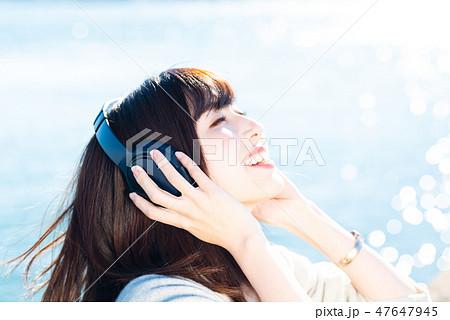 音楽を聴く若い女性 47647945