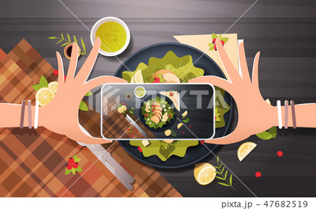 food blogger taking mobile photo of fresh vegetable salad with chicken and sauce in black bowl top 47682519
