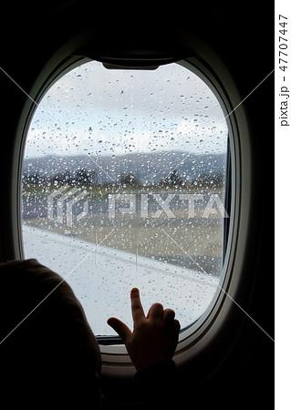 Little boy looking through the plane window 47707447