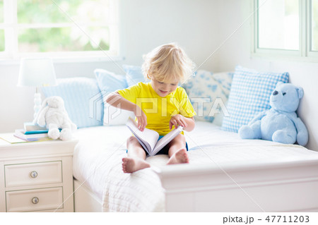 Child playing in bed. Kids room. Baby boy at home. 47711203