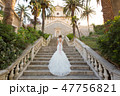 graceful bride climbs the stone stairs in a wedding dress 47756821