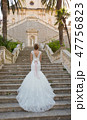 graceful bride climbs the stone stairs in a wedding dress 47756823
