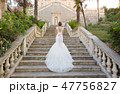 graceful bride climbs the stone stairs in a wedding dress 47756827