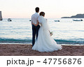 newlyweds stand on the beach and look at the sea 47756876