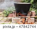 Black cauldron boiling on a bonfire 47842744