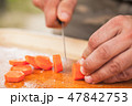 Carrot slicing. Cook hands with knife 47842753