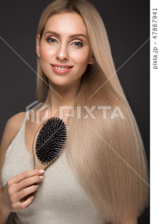 Beautiful blond girl with a perfectly smooth hair, classic make-up with hairbrush in the hands 47867941