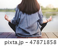 Young Woman Practices Yoga in Lotus Position 47871858