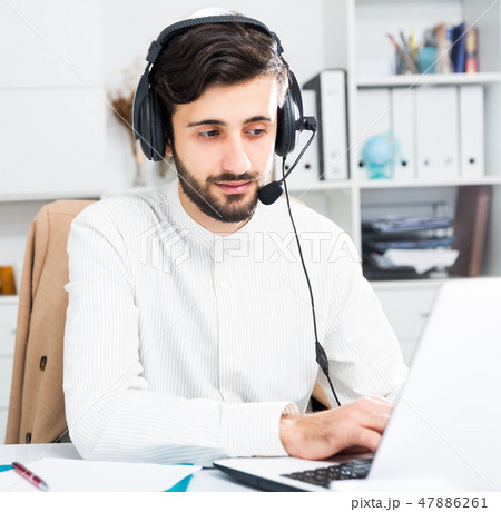 Man with earphones working at office 47886261