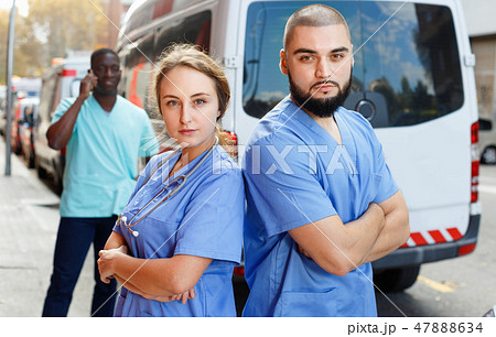 Two confident paramedicals in uniform posing near ambulance car 47888634