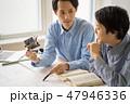 笑顔優しい先輩から一級建築士の試験勉強を教えてもらい嬉しそうに楽しく勉強する若い男性会社員 47946336