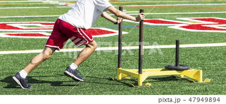Athlete pushing weighted sled on turf field 47949894