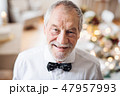 A close-up portrait of a senior man standing indoors in a room set for a party. 47957993